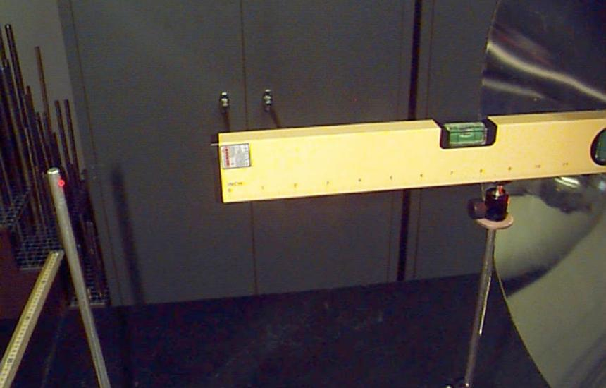 A laser level is used to align the parabolic mirrors with the optical bench. A s