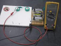 The capacitor is charging and the current shows on the multimeter.